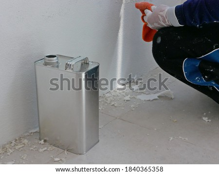 A gallon of thinner placed next to old concrete wall, while a painter is removing sticky rough glue and tape remain on the wall, as a preparation before starting the paint the house Stock photo ©