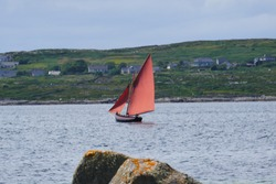 A Galway hooker boat, popular on the west coast of Ireland for red sails and black hull.