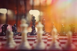 A game of chess set on a chessboard with blurry backgrounds and vintage colors. (focus selected)