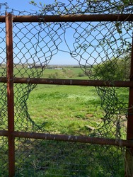 A gap in a wire fence looking through onto a green farmers field.