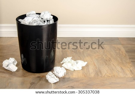 A garbage can with lots of crumpled paper in and around it