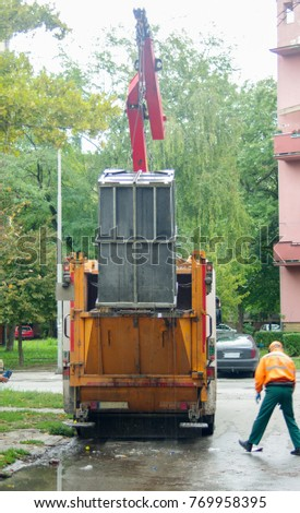 A garbage truck, the moment when it is unloaded from the garbage can in a truck. #769958395