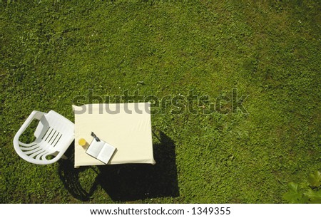 A garden chair, table, glass of orange juice, book and sunglasses, on a lawn. ready for the gardener to take a break. Vertical viewpoint. Space for text on the grass.