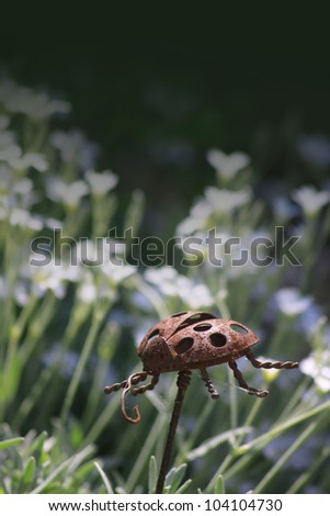 A garden ornament in the form of a rusty ladybird made of steel, set against a floral garden background. Copy space available to top of image.