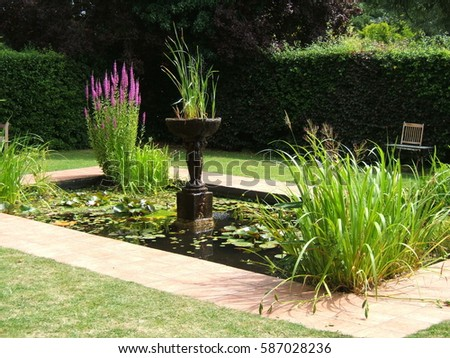 A garden pond with statuary and plants. #587028236