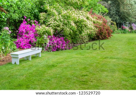 A garden scene with blooming azaleas and a white bench