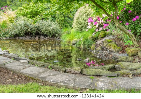 A garden scene with flowers trees and fish pond