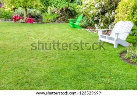 A garden scene with green lawn and benches