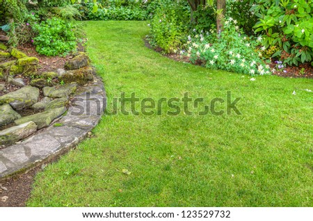 A garden scene with stone edged flower beds