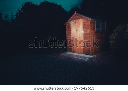A garden shed lit up at night