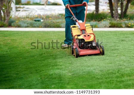 A garden worker takes on a lawn with a lawn mower. Lawn mowing. #1149731393