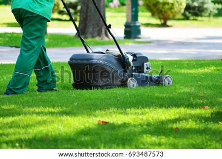 A garden worker takes on a lawn with a lawn mower. Lawn mowing. #693487573