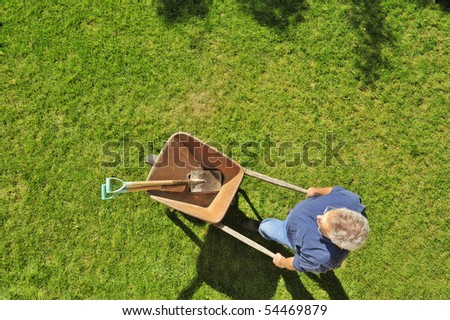 A gardener setting off to work with his wheelbarrow and tools, taken from a high viewpoint. Space for text across top of image