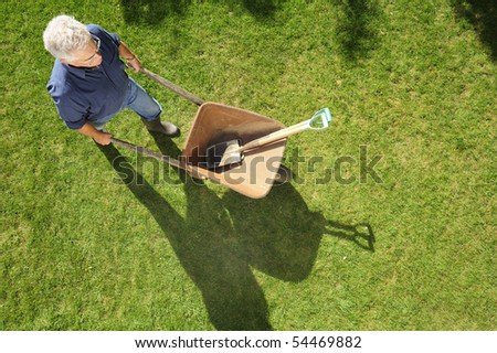 A gardener setting off to work with his wheelbarrow and tools, taken from a high viewpoint. Space for text to right and at base of image