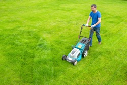 A gardener with a lawn mower is cutting grass in the park. A view from above. A worker is cleaning in the garden.