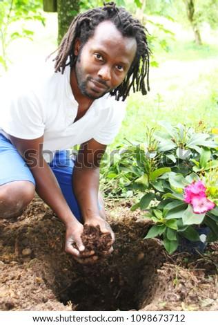 A Gardner planting a flower