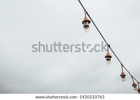 a garland of white light bulbs hanging against a gray sky outdoor. close-up street lighting, copy space. #1420210763