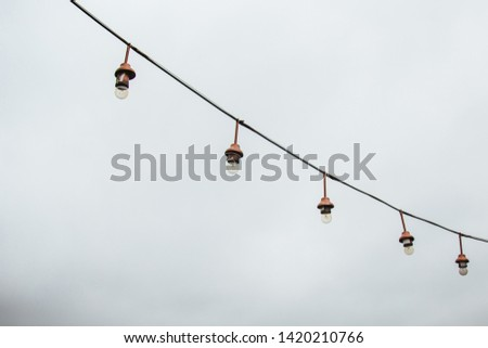 a garland of white light bulbs hanging against a gray sky outdoor. close-up street lighting, copy space. #1420210766