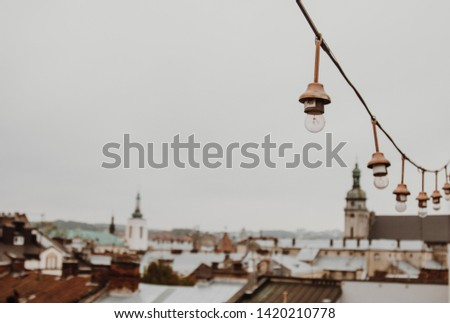 a garland of white light bulbs hanging against a gray sky outdoor. close-up street lighting, copy space. #1420210778