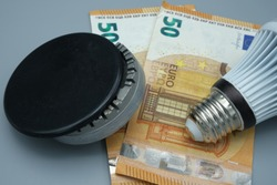 A gas stove with a light bulb nearby, on top of two fifty euro banknotes. Expense concept