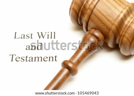 A gavel on top of will papers with the focus on the writing.