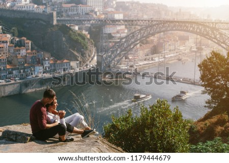 A gay couple traveling and enjoy sunset outdoor, european city view with bridge and river