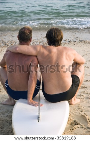 A gay male couple cuddle together while sitting on surfboard at the beach.