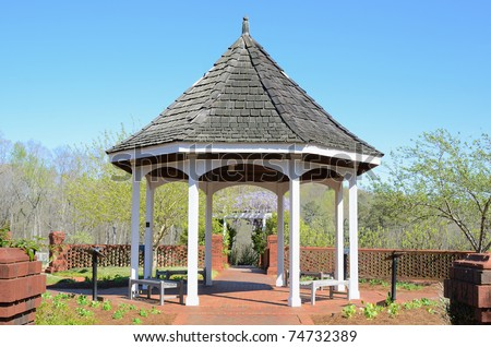 A gazebo surrounded by a brick wall in a little square