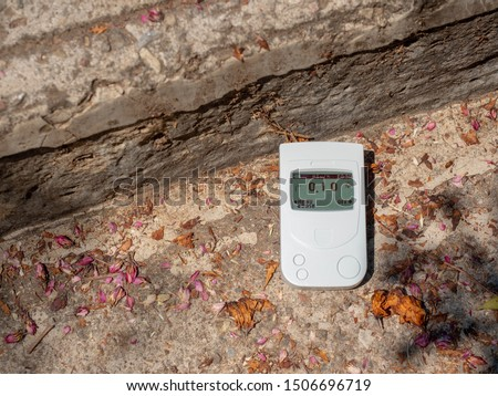 A Geiger counter, a dosimeter on stone steps measures background radiation. Summer, the old ruins of stone houses. Travel Europe. #1506696719