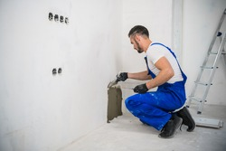 A general laborer in overalls uses a trowel to cover the wall with cement