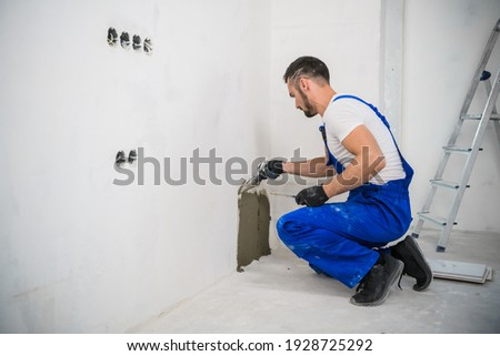 A general laborer in overalls uses a trowel to cover the wall with cement Stock fotó ©