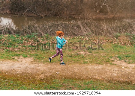 A general shot of a sporty red-haired Caucasian female running while checking her surpluses outdoor Foto stock ©
