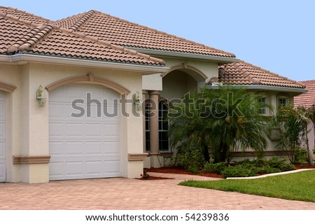a generic one story florida home with garage, palm trees and a clear blue sky