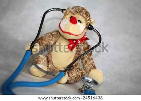 a generic stuffed toy monkey with a doctors stethoscope represents childrens doctors, pediatrics and fun check ups