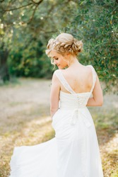 A gentle blonde bride stands by an olive tree in the middle of a grove, back view