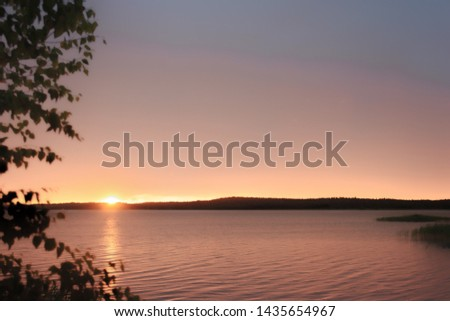 A gentle dawn over the shore of the lake, the sun begins to rise above the opposite shore, dispersing the predawn fog and filling the sky and water with a yellow-pink glow.