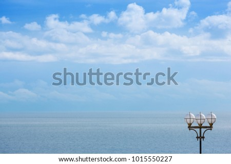 A gentle gentle cloud on the blue sky, a street light and azure sea, a natural background #1015550227