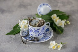 A gentle still-life with a cup of green tea and jasmine flowers. A clock bulb in a cup.