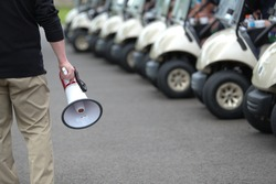 A gentleman holds a megaphone just prior to briefing golfers participating in a golf outing.