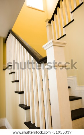 A gently winding staircase inside a large expensive home.