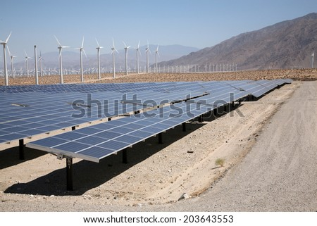 A Genuine Energy Farm in the Hot Arid Desert of Palm Springs California features Solar Panels and Wind Turbines to Harness the Power of Nature to generate free green energy to sell to the masses