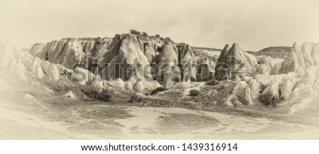A geological formation consisting of volcanic tuff with cave dwelling. Cappadocia in Central Anatolia is a UNESCO World Heritage Site since 1985, Turkey (stylized retro) #1439316914