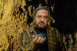A geologist man in clean clothes with glasses holds in his hand a piece of coal on a blurred cave background. Illustration of research on fossil fuels with a non-renewable resource.