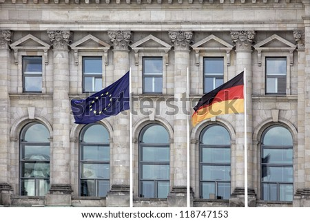 A German and European Union flag in front of the German Bundestag in Berlin.