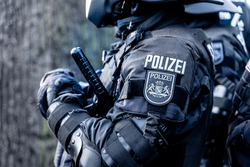 A german police officer is waiting in his riot body protection on a demonstration against the corona-laws. He has a tonfa or baton in his hand and a coat of arms of the city of Bremen on a badge.