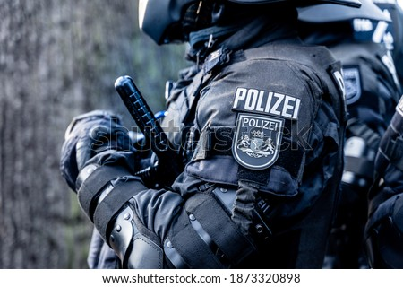 A german police officer is waiting in his riot body protection on a demonstration against the corona-laws. He has a tonfa or baton in his hand and a coat of arms of the city of Bremen on a badge. Stockfoto ©