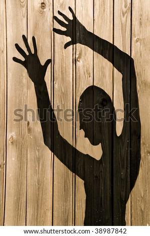 a ghost shadow or silhouette of a woman against a wooden fence with working path