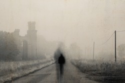 A ghostly blurred figure standing in the middle of the road on an eerie misty morning. Next to a ruined building. With a dark, moody, grunge edit.