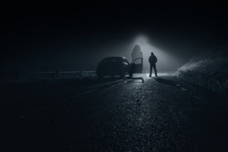 A ghostly blurred woman in a dress standing floating on a country road at night. With a car and driver behind.