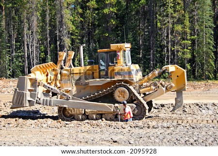 A giant bull dozer moving rocks during road construction in a forested area.